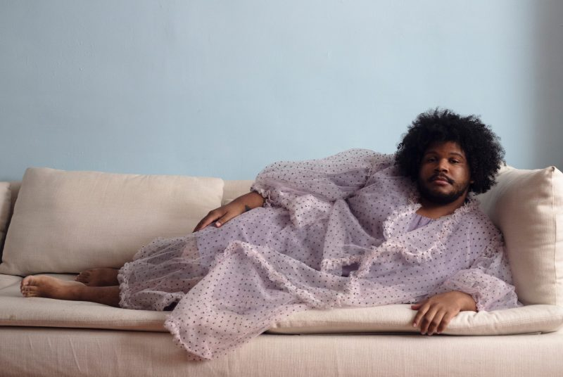 Bassoonist and composer Clifton Joseph Guidry III reclines on an off-white sofa, barefoot and dressed in a  light pink polka dot robe.